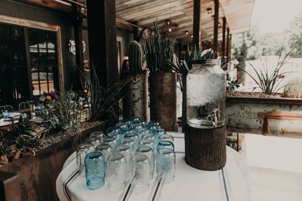 Photo of a jug of water on a table with glasses. Photograph by Austin, Texas wedding photographer Nikk Nguyen.