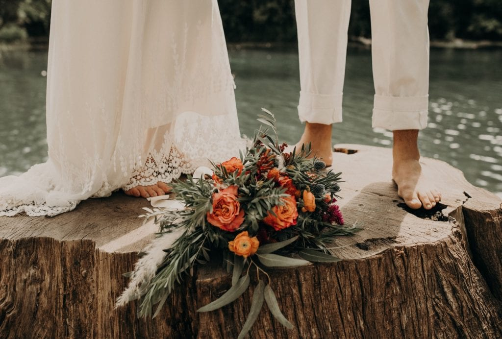 Photo by Austin, Texas wedding photographer Nikk Nguyen of bride and groom standing barefoot on a tree trunk with a beautiful wedding bouquet