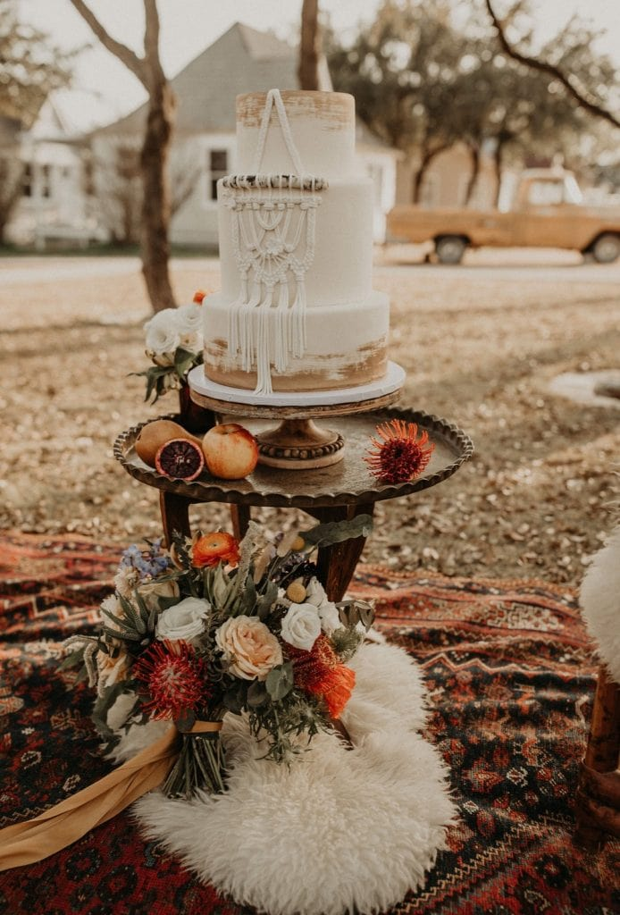 beautiful white, bohemian styled wedding cake on a table. Photograph by Austin, Texas wedding photographer.