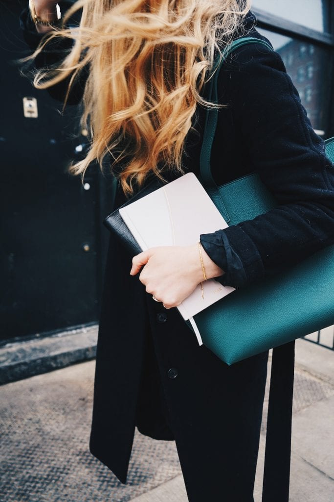 Blond woman holding a white planner against her black purse on her left shoulder.