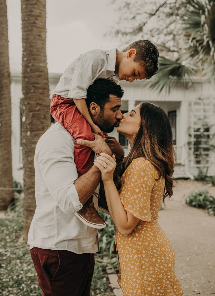 Photo by Austin, Texas wedding photographer Nikk Nguyen Photo of a family, couple gives each other a kiss while the child sits on the father's shoulders