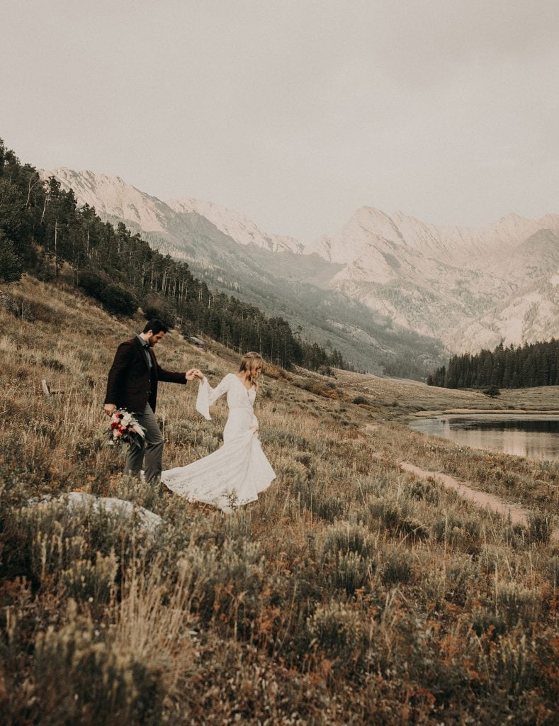 Photo by Austin, Texas wedding photographerNikkolas Nguyen of a bride and groom walking down a field in the mountains at Piney River Ranch in Vail, Colorado.
