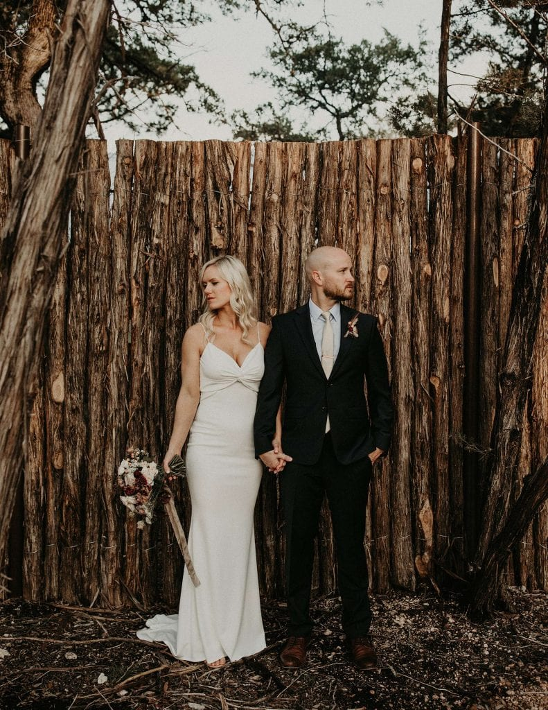 Bride and groom holding hands while standing next to one another but looking in opposite directions in front of a wooden fence at Lucky Arrow Retreat in Dripping Springs, Texas. Photograph by Austin, Texas wedding photographer Nikk Nguyen.