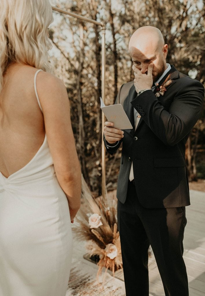 A groom stands outside weeping as he reads his wedding vows to his bride at Lucky Arrow Retreat in Dripping Springs, Texas. photographed by Austin Texas wedding photographer Nikkolas Nguyen