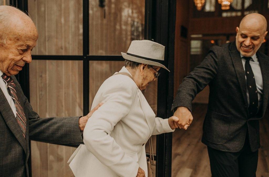 Two men assist an elderly woman as she walks through a door for a wedding, photographed by Austin Texas wedding photographer Nikkolas Nguyen