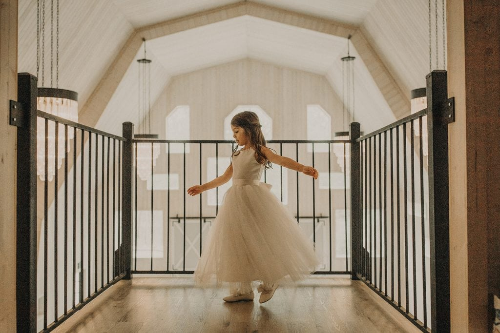 A young flower girl twirls in her dress while at a wedding at Dove Hollow Estate in Longview, Texas by Austin Texas wedding photographer Nikkolas Nguyen
