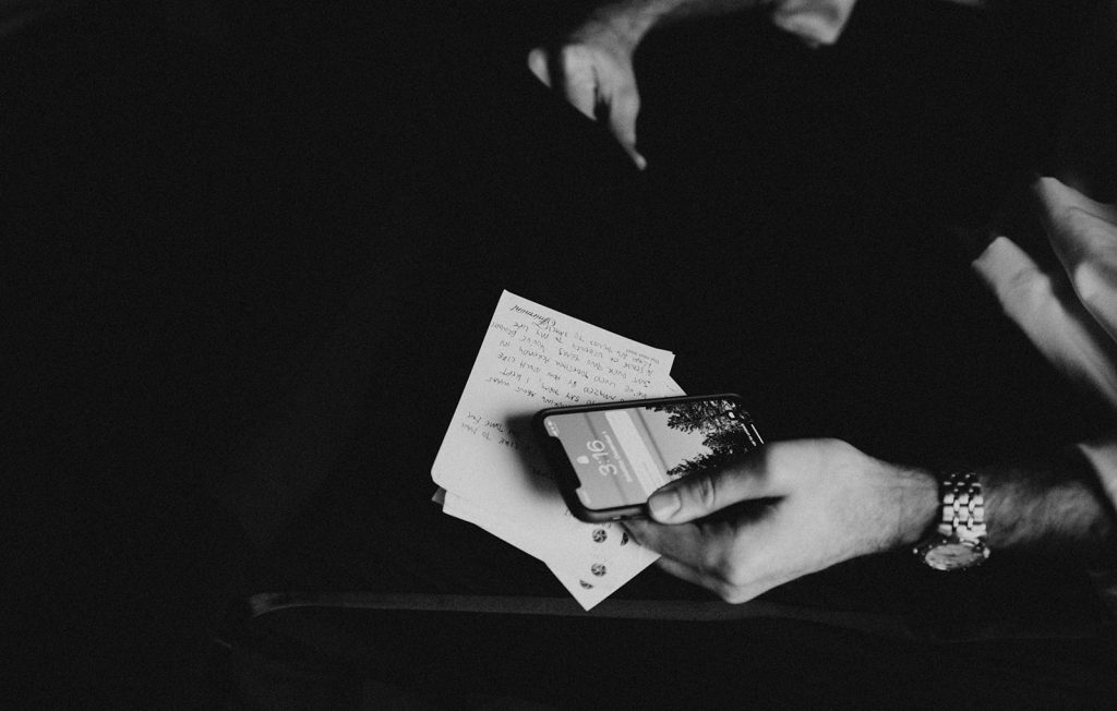 Photo by Austin, Texas wedding photographer Nikkolas Nguyen of a hand holding a hand-written card and a phone