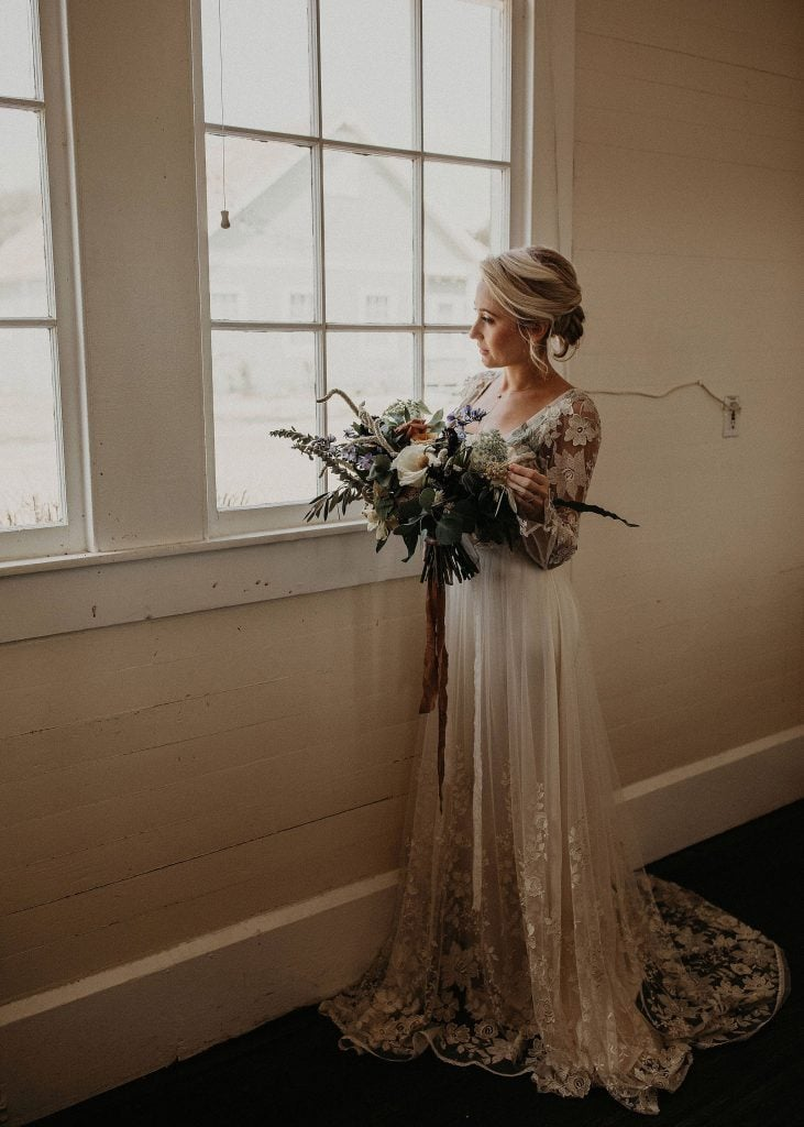Photo by Austin, Texas wedding photographer Nikkolas Nguyen of a bride with beautiful bohemian dress and boho wedding bouquet staring out of a window at Star Hill Ranch