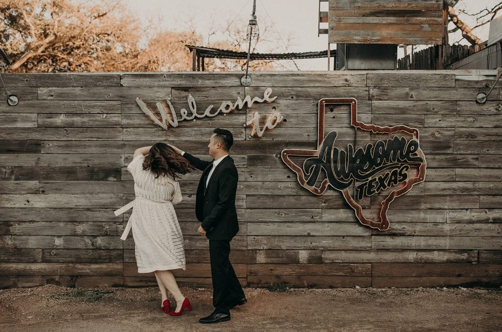"Photo by Austin, Texas wedding photographer Nikkolas Nguyen of a couple dancing in front of a sign that reads ""Welcome to Awesome Texas"""