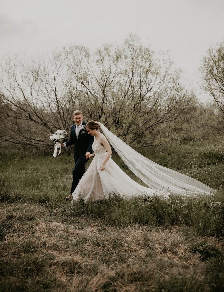 Photo by Austin, Texas wedding photographer Nikkolas Nguyen, of a bride and groom walking in a meadow in Austin, Texas in a beautiful wedding dress