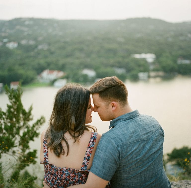 Bride to be and groom to be smiling at each other as their foreheads touch while sitting on Mt Bonnell in Austin, Texas photographed by Austin, Texas wedding photographer Nikk Nguyen.