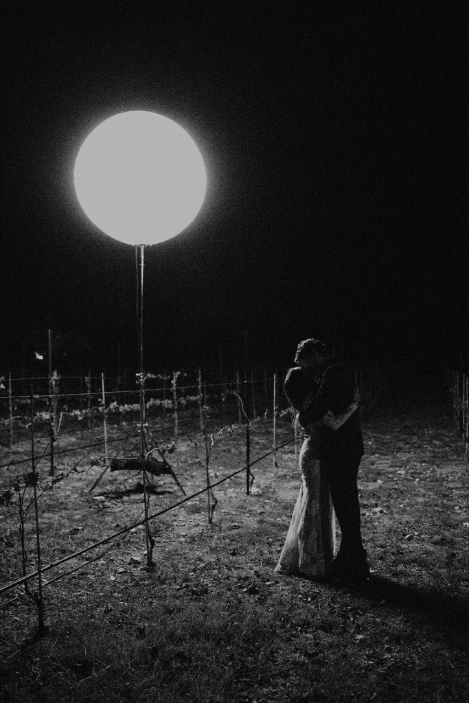 Black and white photo of a couple kissing in a vineyard at night under a light. by Austin, Texas wedding photographer Nikkolas Nguyen,