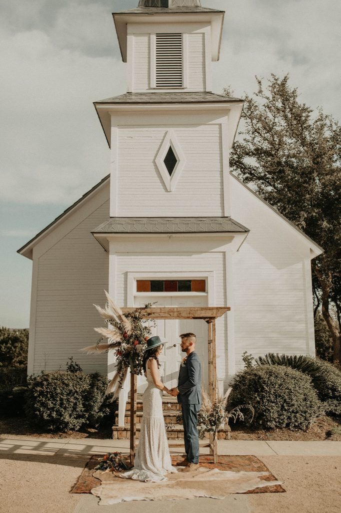 Photo by Austin, Texas wedding photographer Nikkolas Nguyen of a wedding couple standing in front of a white wedding chapel at Star Hill Ranch