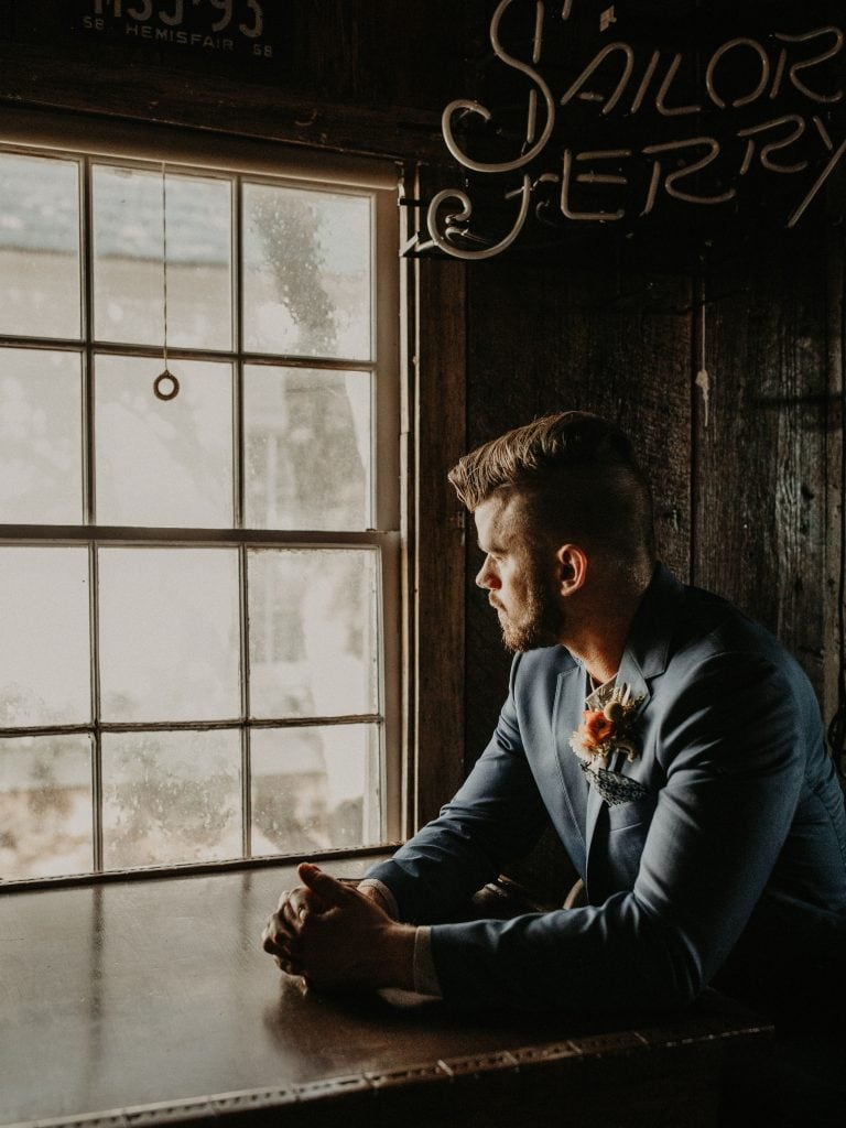 Photo by Austin, Texas wedding photographer Nikkolas Nguyen of a groom starting out side of a window of a rustic cabin at Star Hill Ranch