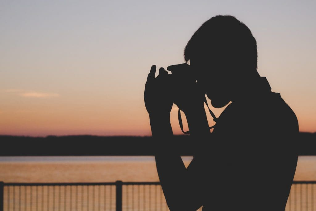 Photo of a silhouette of a man photographing a sunset.