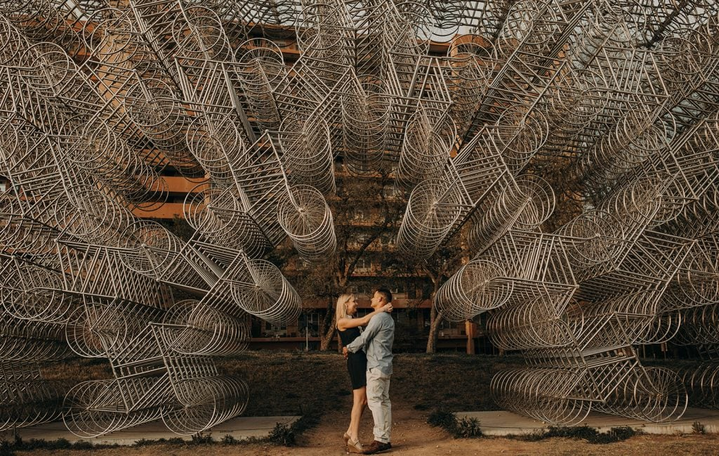 Photo by Nikkolas Nguyen of a couple standing in front of an installation of bikes called Ai Weiwei's Forever Bicycles in Austin, Texas