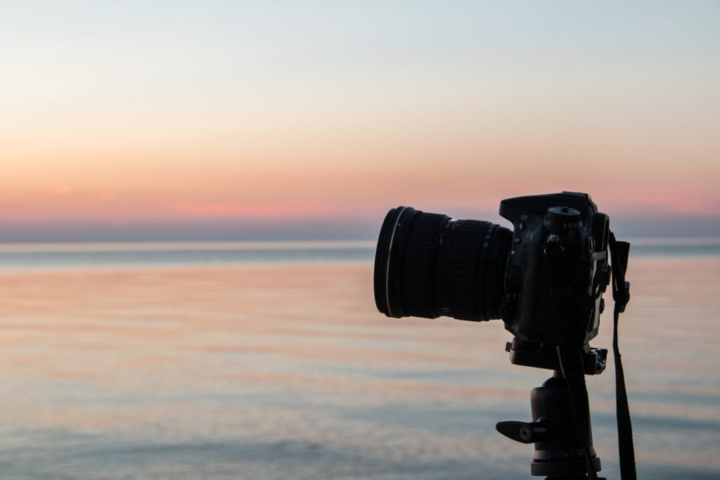 Photo of a camera on a tripod in front of a lake during blue hour.