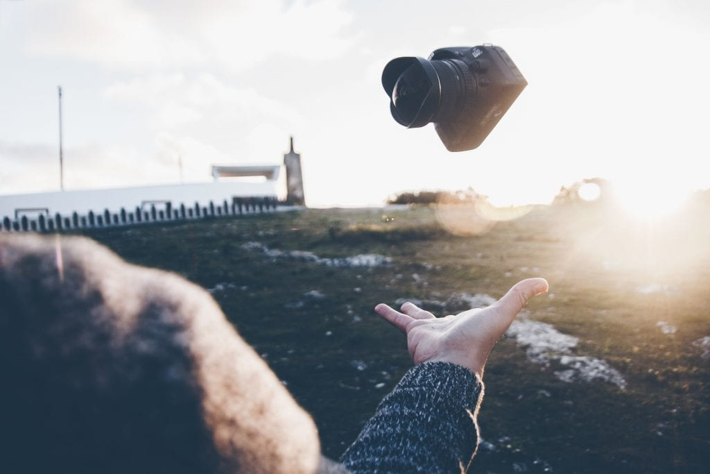 Camera falling into an outstretched hand with sunset in the background