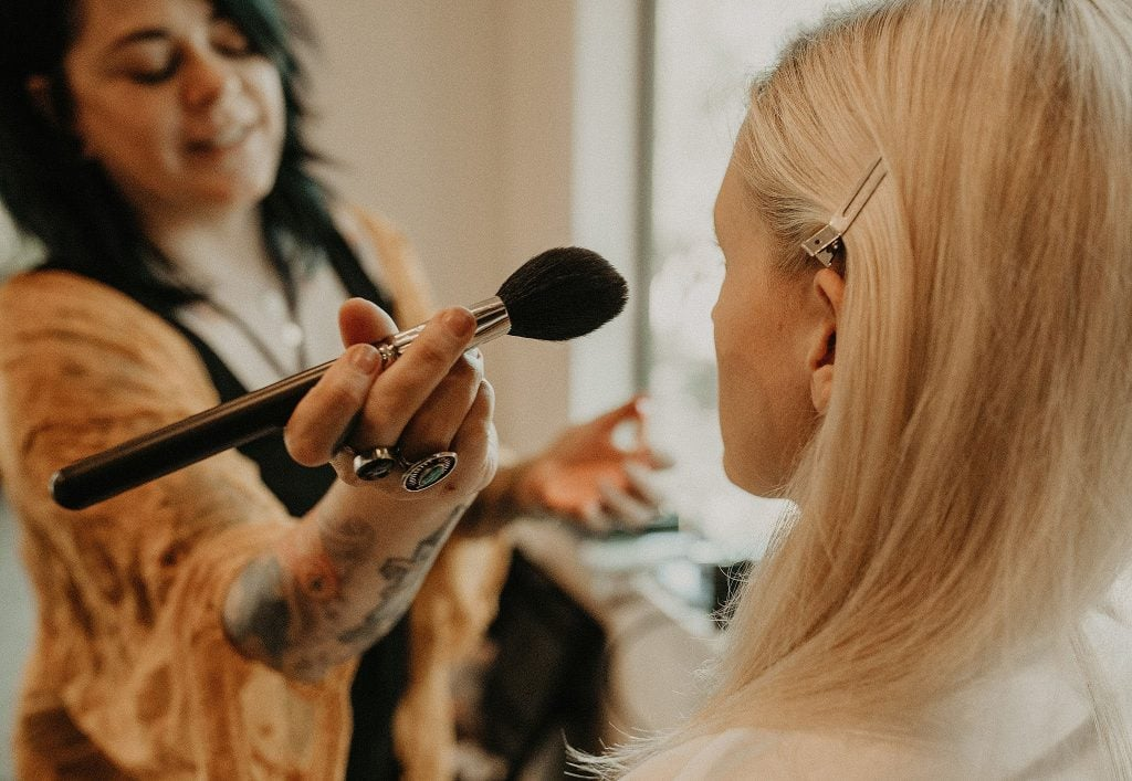 Photograph of an Austin makeup artist applying blush to a bride's face, Photographed by Austin, Texas wedding photographer NIkk Nguyen