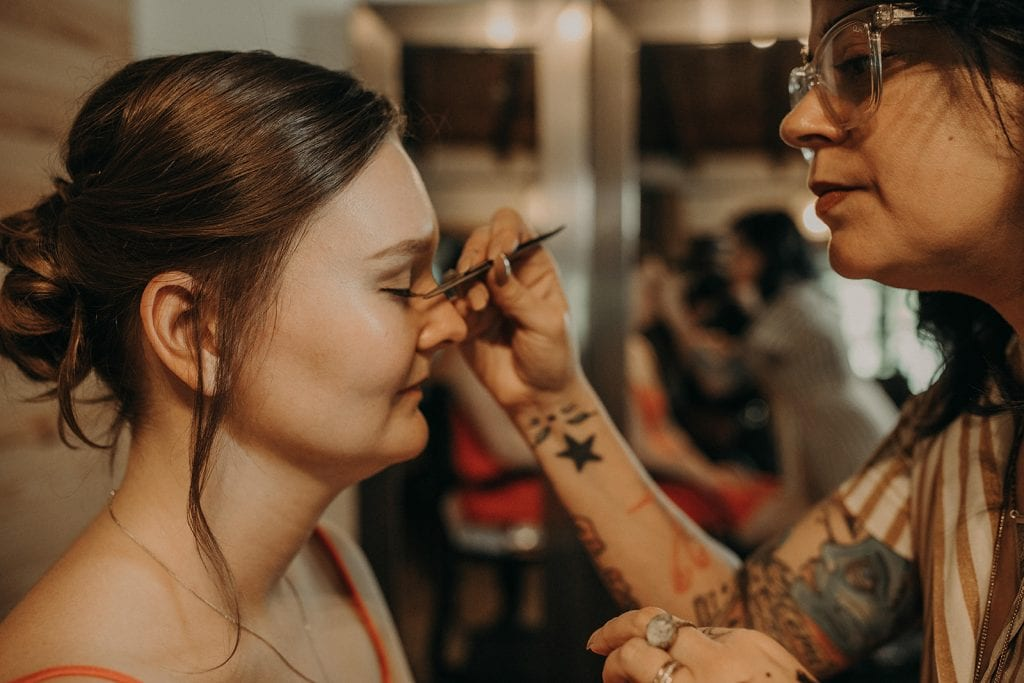 Photo of a bride getting her wedding makeup done by a makeup artist, Photographed by Austin, Texas wedding photographer NIkk Nguyen