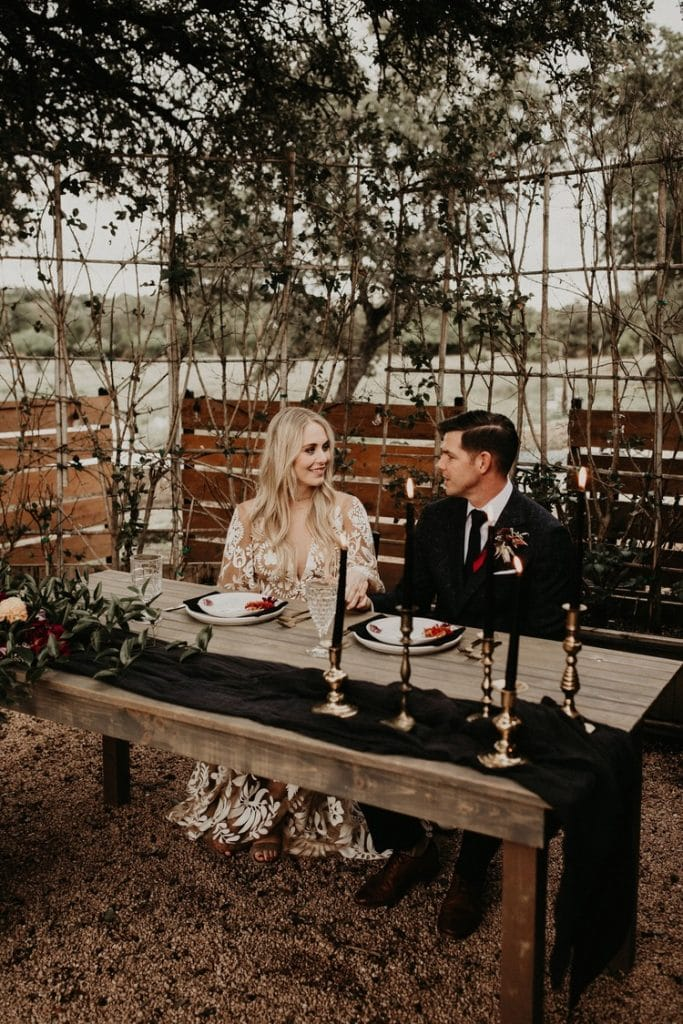 A bride and groom sitting at a nicely set table, photographed by Austin, Texas wedding photographer NIkk Nguyen