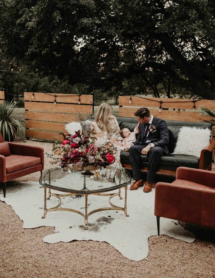 A wedding couple sitting in a lounge area outside with their child, photographed by Austin, Texas wedding photographer NIkk Nguyen