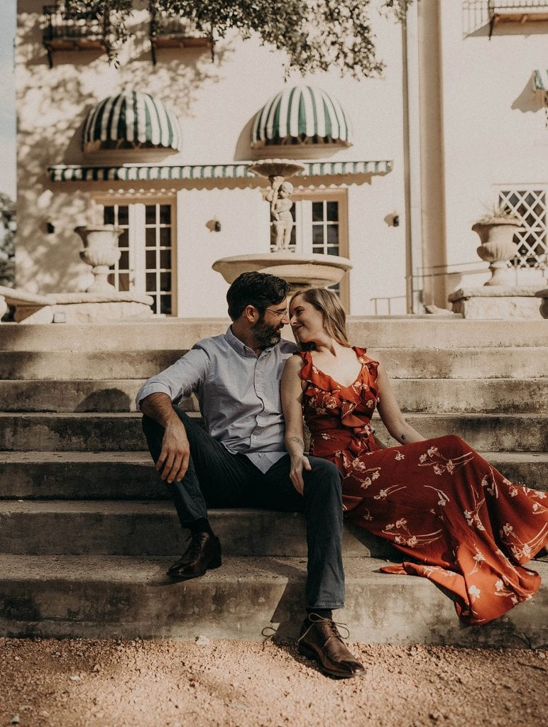 A couple sitting on steps outside in Austin in the shade, Photographed by Austin, Texas wedding photographer NIkk Nguyen