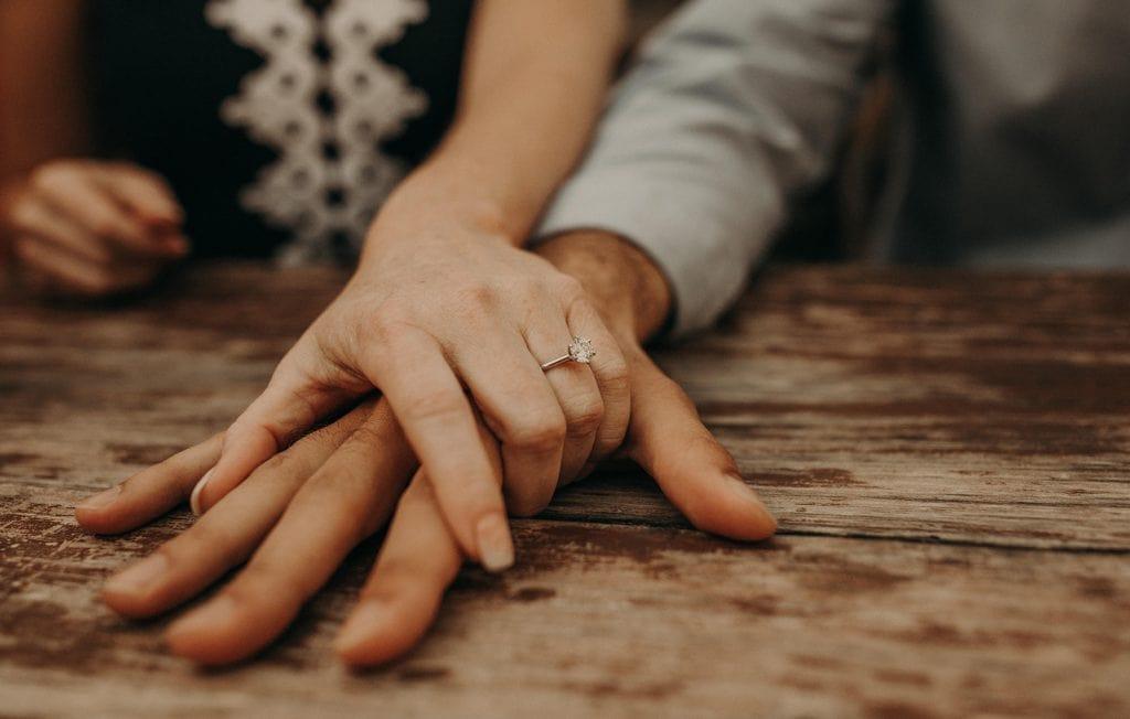Engaged couple holding hands, showing a engagement ring, photographed by Austin, Texas wedding photographer Nikk Nguyen