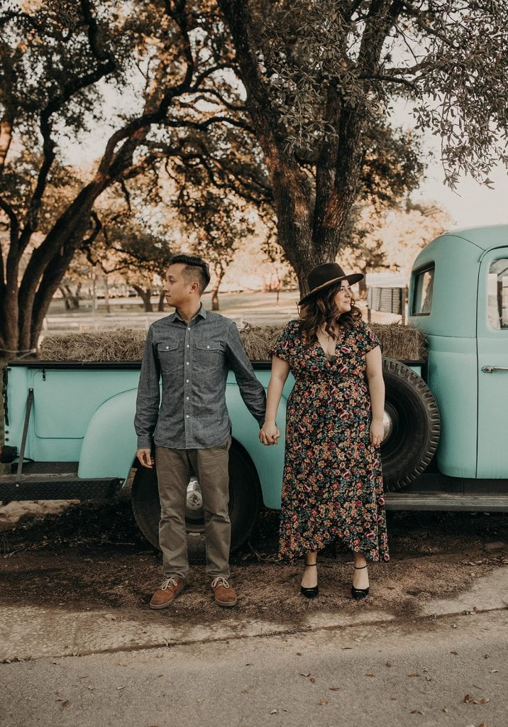 Engaged couple standing in front of vintage truck, photographed by Austin, Texas wedding photographer Nikk Nguyen