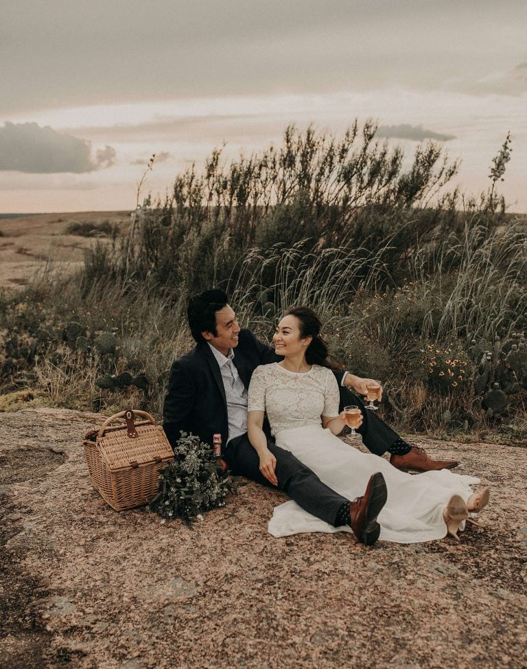 Bride sitting between groom's legs and turned to look at him as they smile at each other while sitting on Enchanted Rock in Fredericksburg, Texas and tall grass behind them. A picnic basket sits to the right of the groom with the bride's bouquet and a bottle of champagne. The bride and groom are both holding a glass full of champagne in their left hands. Photographed by Austin, Texas wedding Photographer Nikk Nguyen