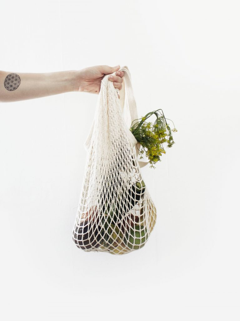 Photo of a hand holding a reusable grocery bag