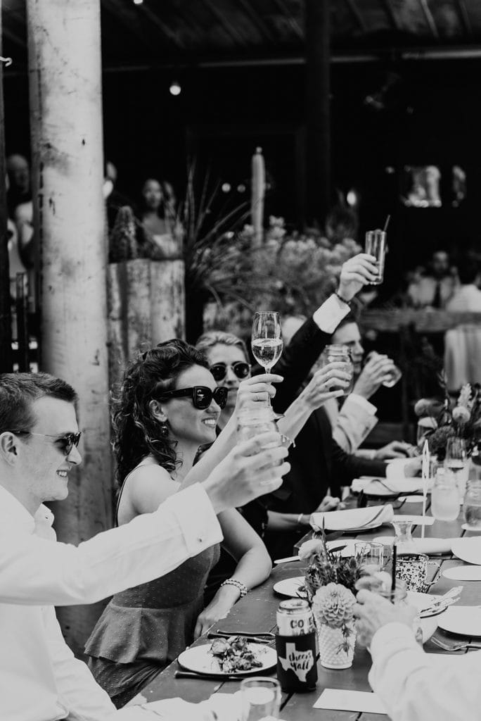 Photo of wedding guests raising their glass, photographed by Austin, Texas wedding photographer NIkk Nguyen