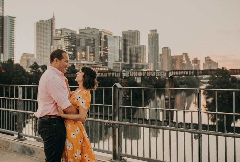 during a sunrise engagement shoot a Groom to be holding bride to be around her waist as they stare longingly into each other's eyes and smile on a bridge in front of the city skyline in downtown Austin, Texas. Photograph by Austin, Texas wedding photographer Nikk Nguyen.