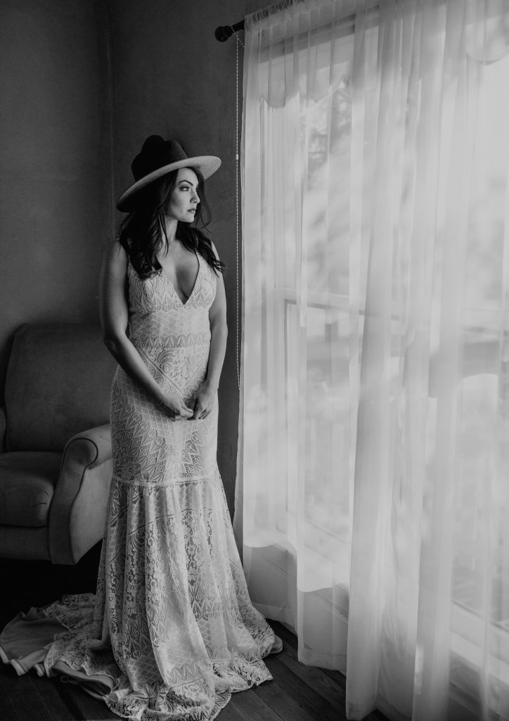 Photo of a bride staring out of a window, photographed by Austin, Texas wedding photographer Nikk Nguyen