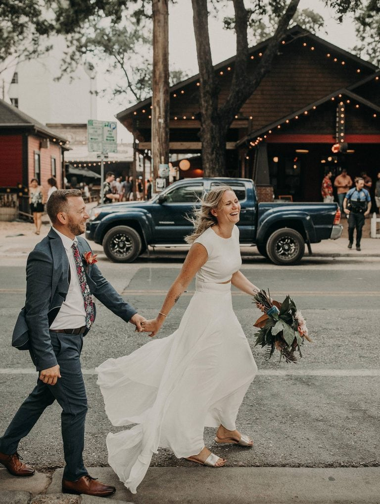 Bride holding groom's hand as they smile and leads him down Rainey Street in Austin, Texas in front of restaurant. Photograph by Austin, TX wedding photographer Nikk Nguyen.