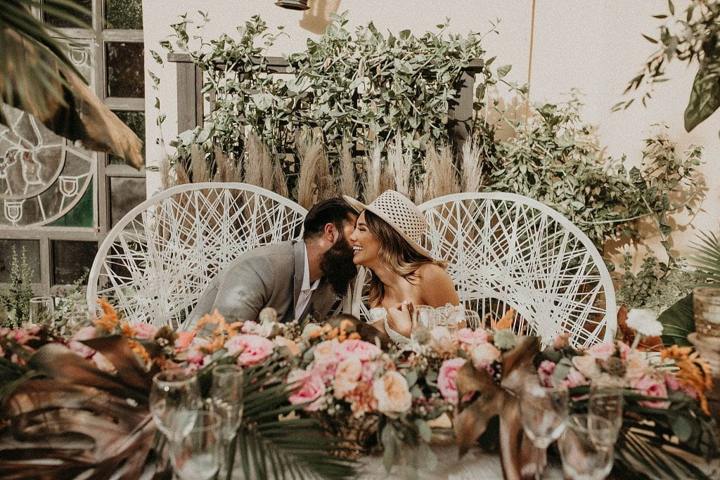 Groom leans over and whispers in brides right ear as she smiles and they sit in white wicker chairs in front of an extravagantly decorated wedding table at Hotel El Convento in Old San Juan, Puerto Rico. Photograph by Austin, Texas wedding photographer Nikk Nguyen.