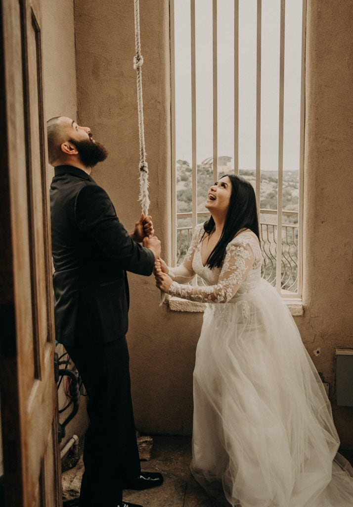 A bride and groom ringing the bell of their wedding chapel, Photographed by Austin, Texas wedding photographer NIkk Nguyen