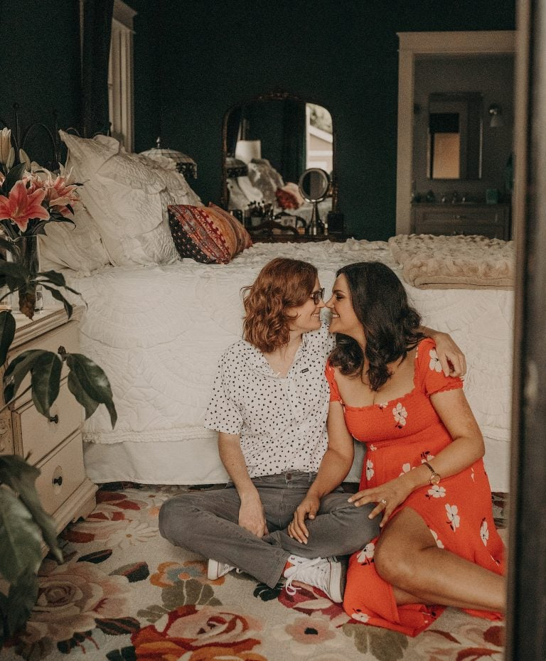 two woman sitting on the floor on the side of their bed while smiling at each other and one partner has her arm resting on her partners knee in a home in East Austin, Texas. Photographer by Austin Texas wedding photographer Nikk Nguyen.