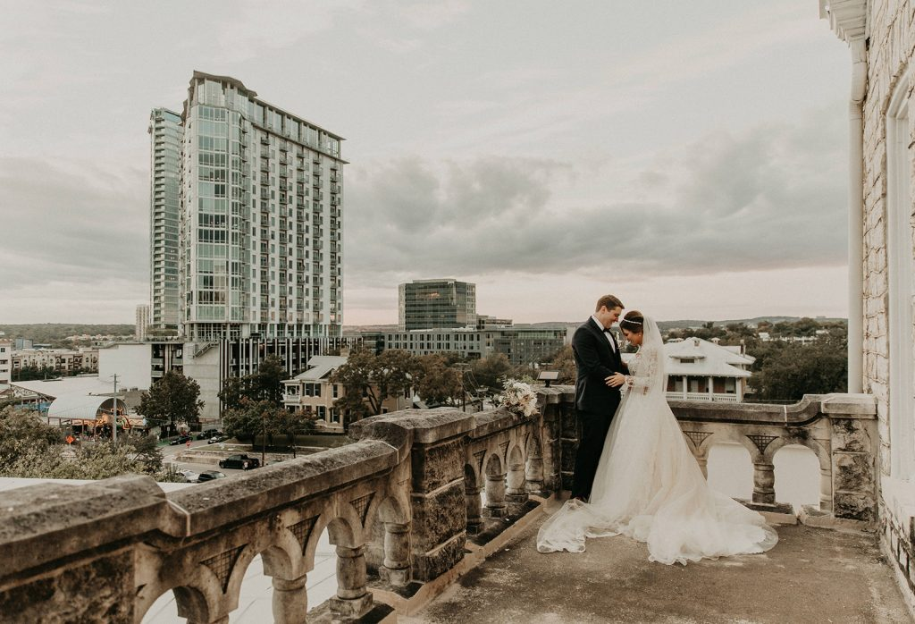 A bride and groom standing on a balcony of a historical building in Austin, Texas, photographed by Austin, Texas wedding photographer NIkk Nguyen