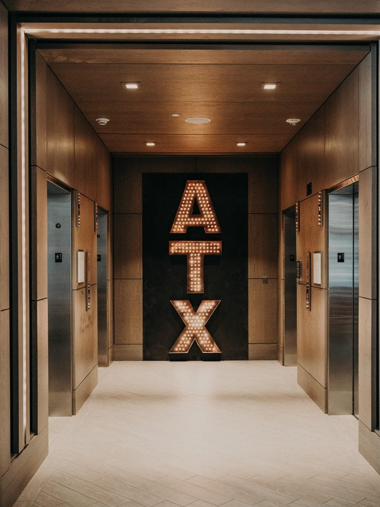 Sign of lit letters spelling ATX in a hotel hall, Photographed by Austin, Texas wedding photographer NIkk Nguyen
