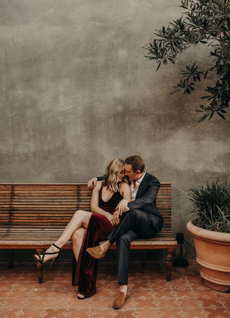 a man in a suite sits on a bench with his arm around a woman in a black dress during their engagement photo session in San Antonio, Texas by Wedding Photographer Nikk Nguyen