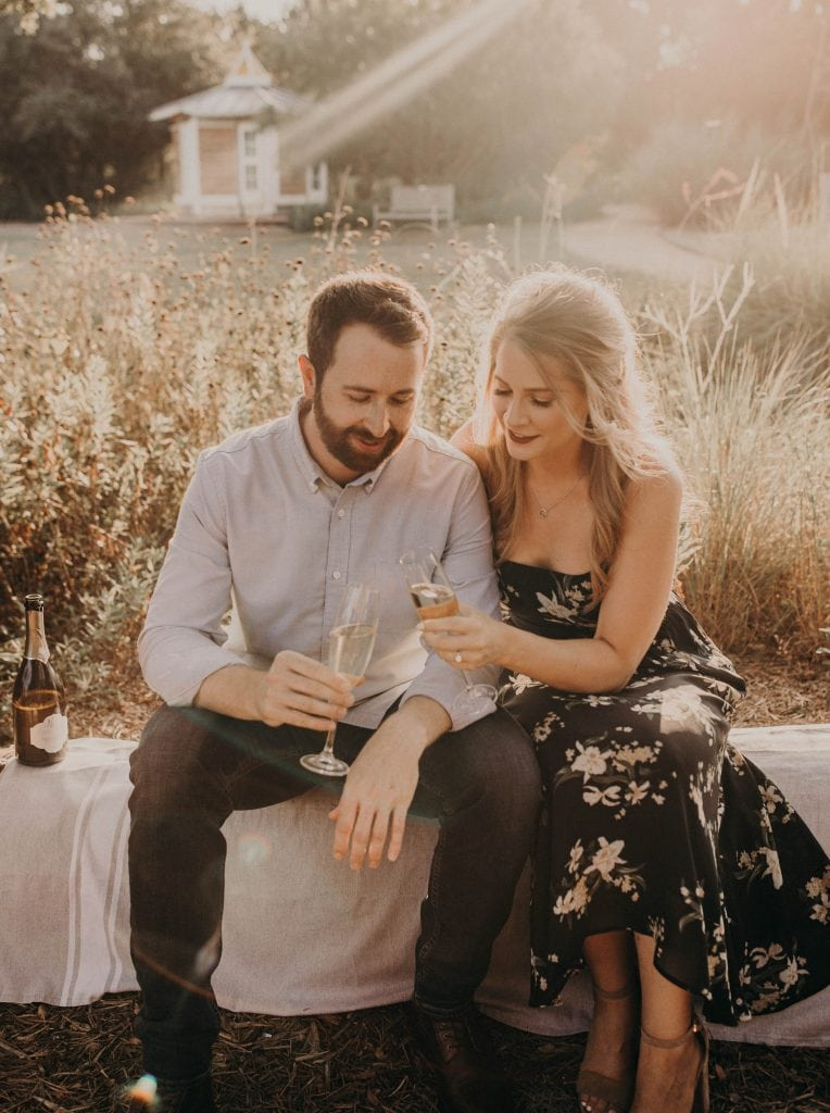 An engaged couple are drinking champagne together at Lady Bird Johnson Wildflower Center in Austin, Texas, Photographed by Austin, Texas wedding photographer NIkk Nguyen