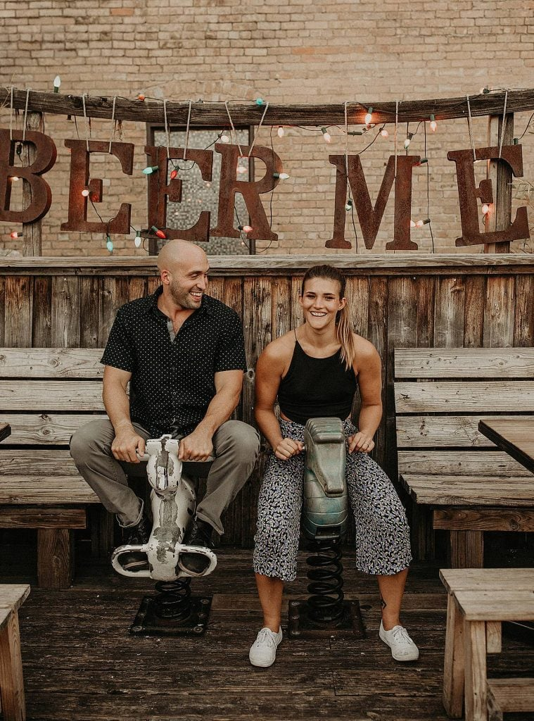 Bride to be and groom to be sitting on spring riders in front of a wooden fence and wooden benches with a lighted sign above them that says