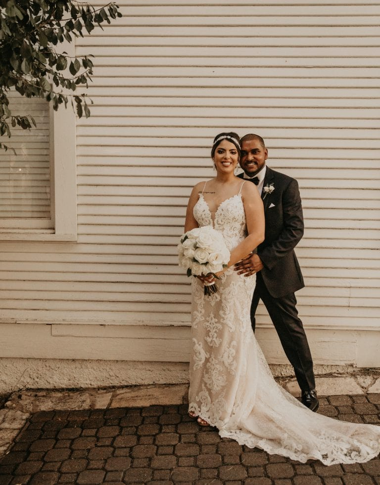 Groom stands behind bride while holding her at the waist as they smile at the camera and she holds her white rose bouquet in front of the white siding of The Allan House in Austin, Texas. Photograph by Austin, TX wedding photographer Nikk Nguyen.