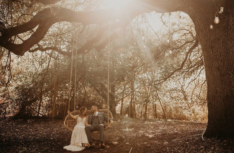 Bride and groom smile at each other as they are sitting in a hammock swing under a large oak tree in a woodsy area during golden hour at Mercury Hall in Austin, Texas. Photograph by Austin, TX wedding photographer Nikk Nguyen.