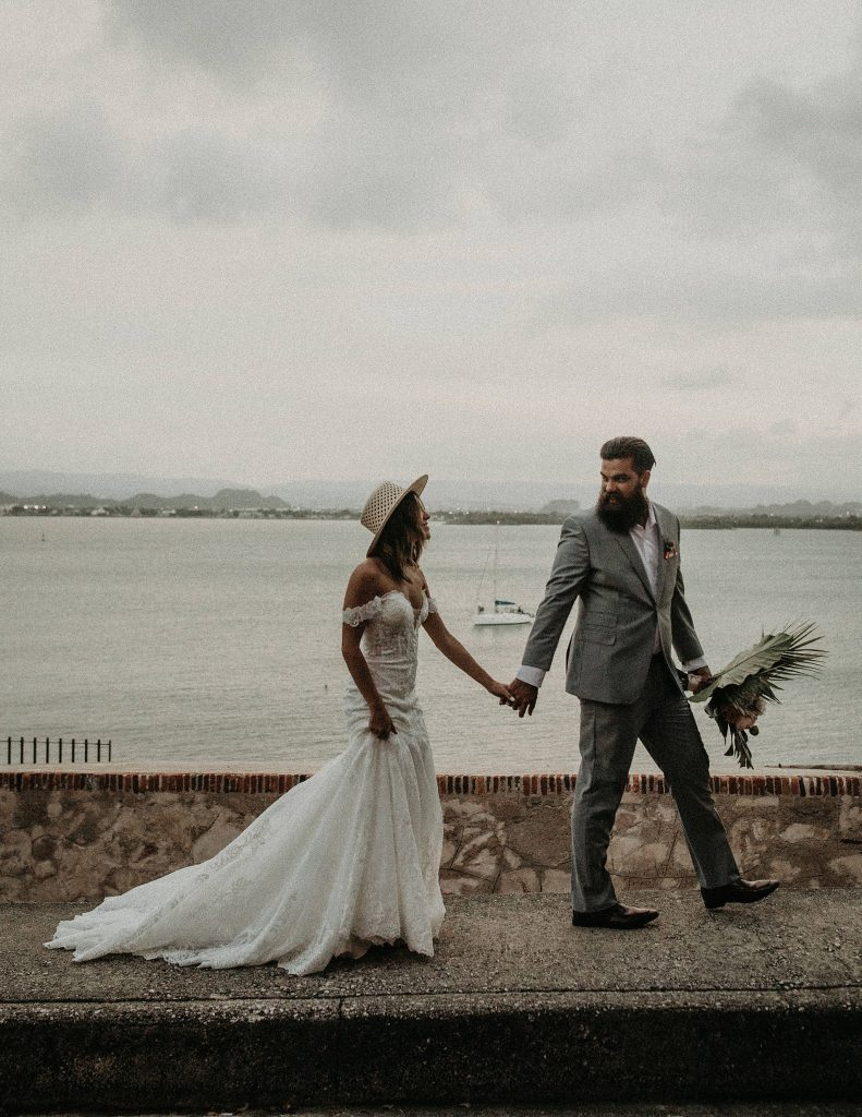 A bride and groom walking past the bay in Puerto Rico, photographed by Austin, Texas wedding photographer NIkk Nguyen