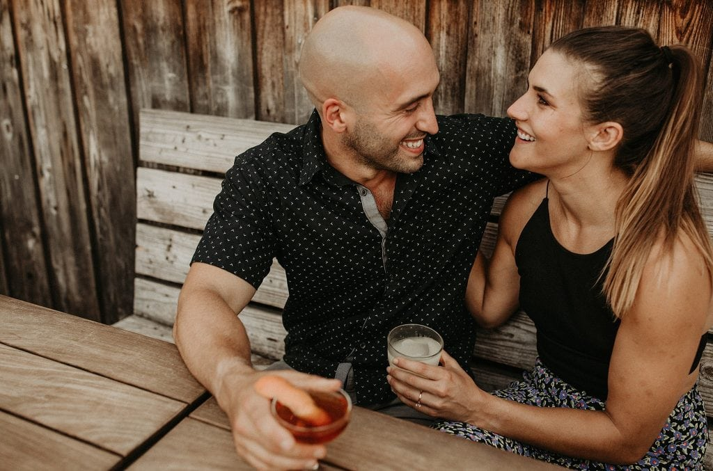 An engaged couple drinking beer at a bar in downtown Austin, photographed by Austin, Texas wedding photographer NIkk Nguyen