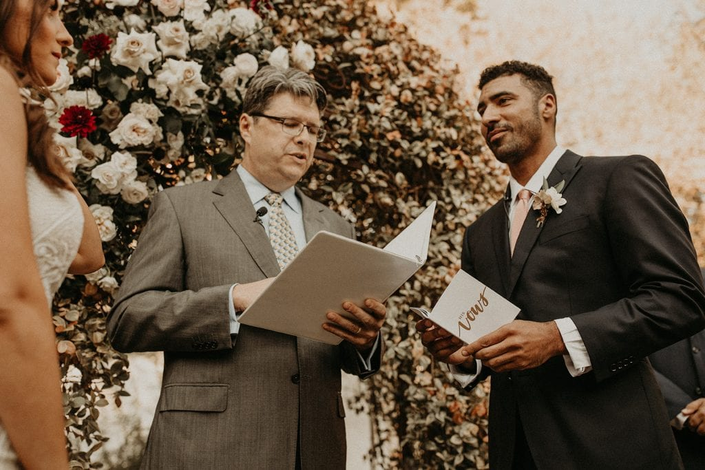 A multilingual wedding officiant announces the bride and groom sharing their wedding vows during a wedding ceremony in Austin, Texas. Photographed by Austin, Texas wedding photographer NIkk Nguyen