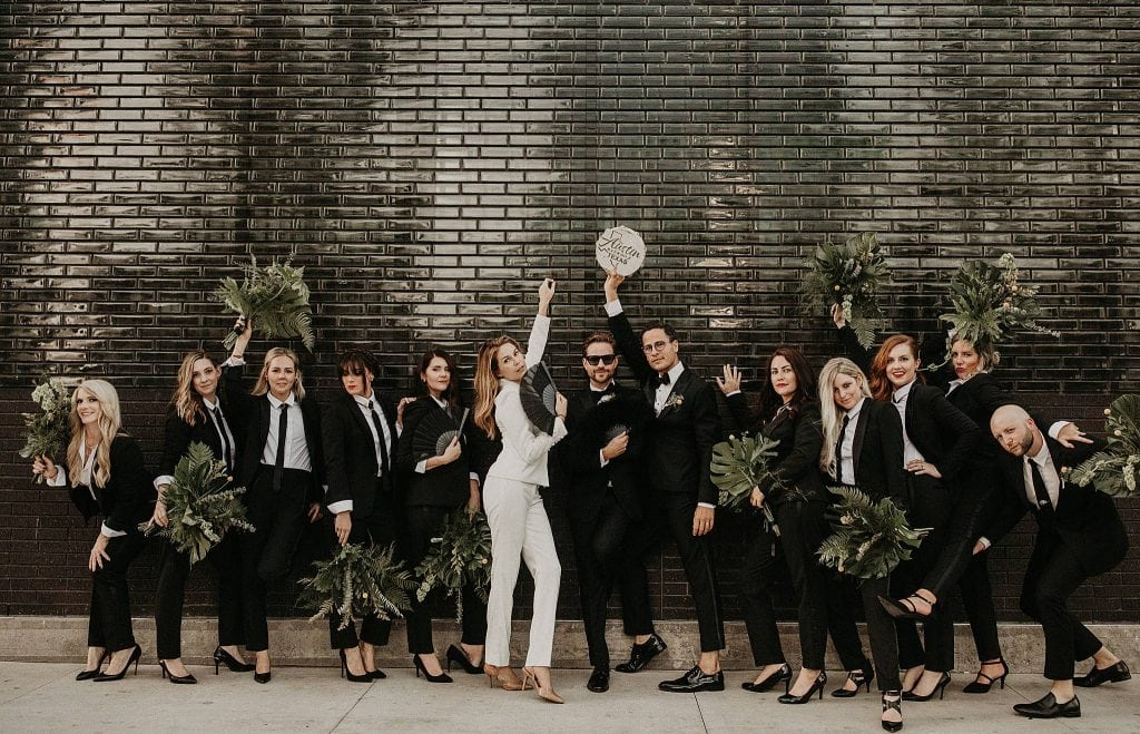 A male couple strike a pose with their wedding party, who are dressed in tuxedos, in front of a black glossy brick wall on the streets of Austin, Texas. Photograph by Austin, TX wedding photographer Nikk Nguyen.
