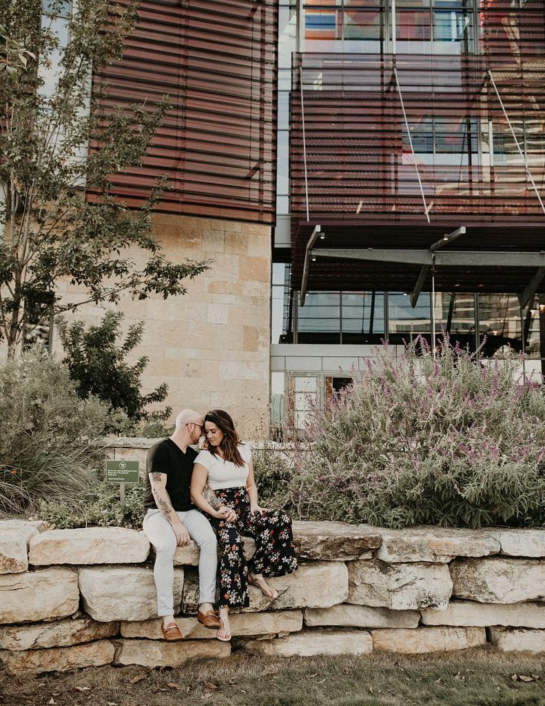 Engaged couple sits with their heads nuzzled together and holding hands on a rock ledge in front of Austin Central Library in the Seaholm District of downtown, Austin, Texas. Photograph by Austin, TX wedding photographer Nikk Nguyen.